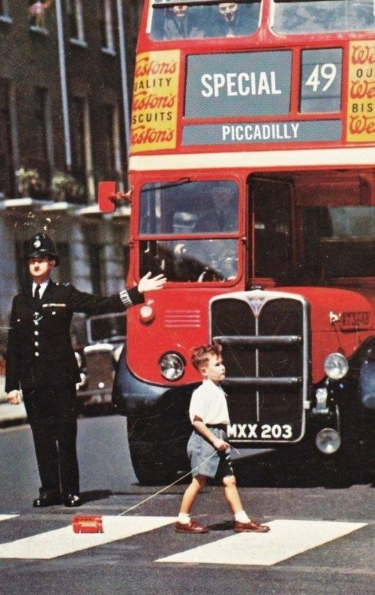 პატარა ბიჭი კვეთს ქუჩას, ხელში თოკზე მობმული სათამაშო ავტობუსით. ლონდონი (1960წ)