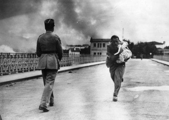 ჟურნალისტი რეიმონდ უოკერი გარბის ხიდზე ბავშვით ხელში, რომელიც ესპანეთის სამოქალაქო ომის დროს გადაარჩ